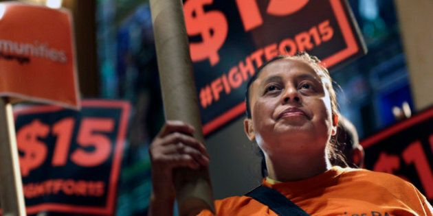 Demonstrators rally for a $15 minimum wage before a meeting of the wage board in New York, Monday, June...