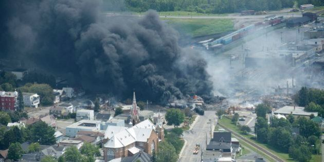 Smoke rises from railway cars that were carrying crude oil after derailing in downtown Lac Megantic,...