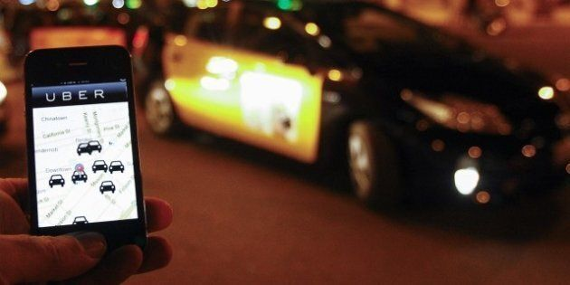 The Uber app is seen on a smartphone past cabs waiting for clients near the Sagrada Familia in Barcelona,...