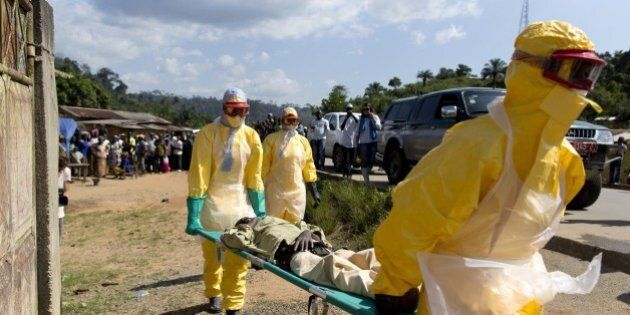 Health workers wearing protective suits carry a patient suspected of having Ebola on their way to an...
