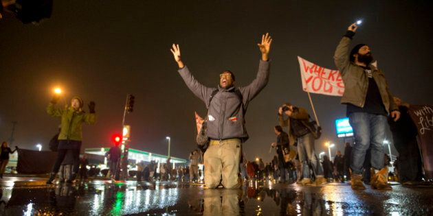 Anthony Grimes kneels on a rain-soaked street as he blocks traffic with other protesters Sunday, Nov....