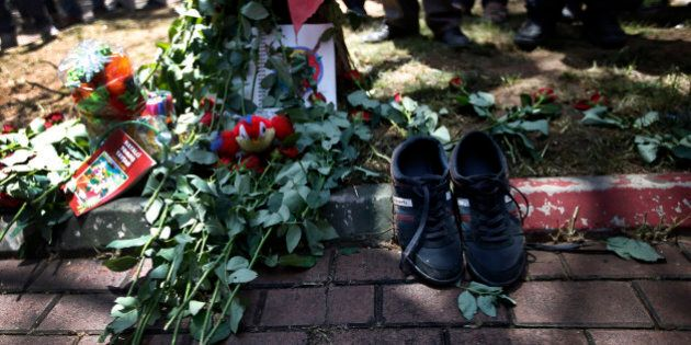 A pair of shoes belonging to a victim are seen next to flowers, laid down by mourners at the site of...