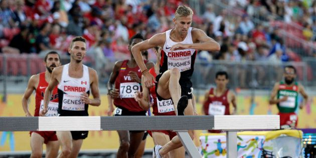 Canada's Matt Hughes jumps over a hurdle during the finals of the men's 3000 meter steeplechase at the...