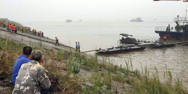 Chinese villagers watch as rescue teams head out to search for survivors of a passenger ship carrying...