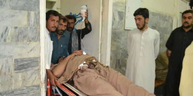 Local residents help an injured bus driver at a hospital in Quetta on May 29, 2015, after unidentified...