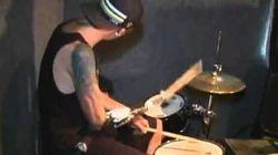 Un musicien joue de la batterie...avec un