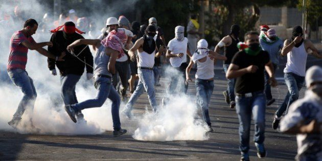 Palestinian protesters stand amid smoke after Israeli forces fired tear gas during clashes in Shuafat,...
