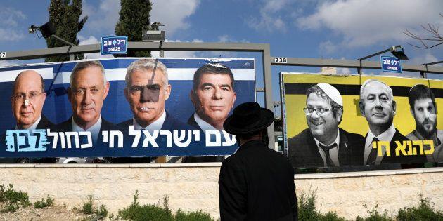 Un homme juif orthodoxe regarde l'affiche de la campagne électorale du parti Bleu-blanc, qui montre ses...