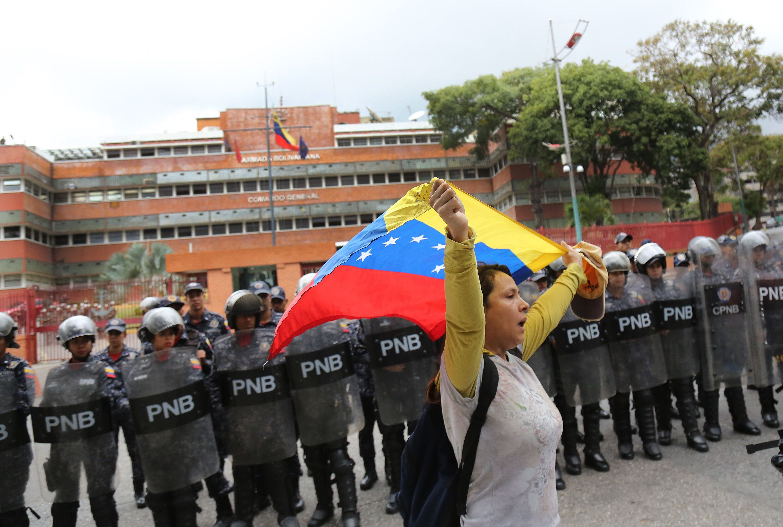 Manifestante protesta contra o regime de Maduro em frente a quartel em