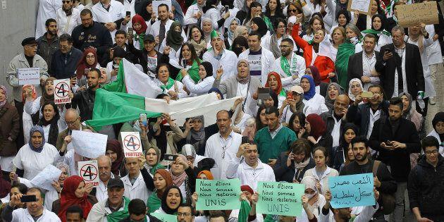 Des Algériens défilent avec des banderoles et des drapeaux lors d'une manifestation à Alger, en Algérie....