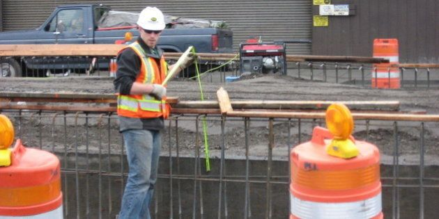 """This worker is """"measuring twice and cutting once."""" He's working on the new First Avenue S ramp from the Spokane Street Viaduct."""