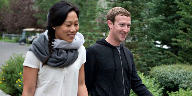 Mark Zuckerberg, chief executive officer and founder of Facebook Inc., walks with his wife Priscilla...