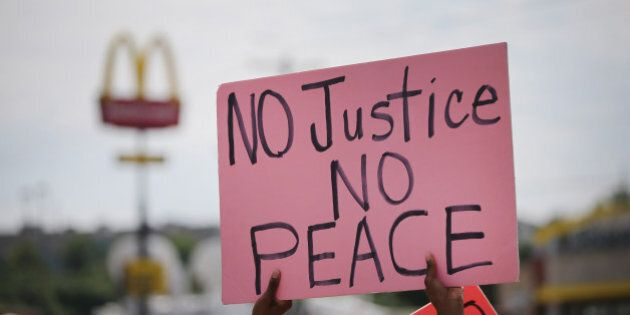 FERGUSON, MO - AUGUST 19: Demonstrators protest the killing of teenager Michael Brown on August 19, 2014...