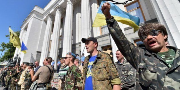 Maidan self-defence activists shout slogans in front of the Ukrainian parliament building in Kiev on...