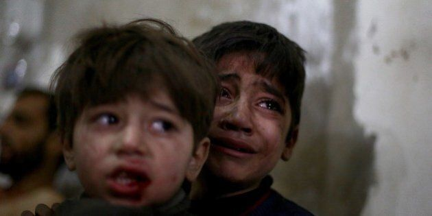 Syrian children react as they wait for treatment at a makeshift hospital in the rebel held area of Douma,...