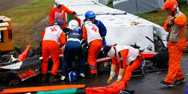 SUZUKA, JAPAN - OCTOBER 05: Jules Bianchi of France and Marussia receives urgent medical treatment after...