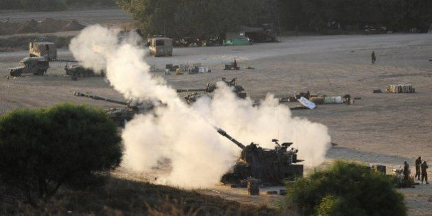 An Israeli tank fires a 155mm shell towards targets in the Gaza Strip from their position near Israel's border with the Palestinian enclave on July 23, 2014. The UN Human Rights Council on Wednesday launched a probe into the Gaza offensive, backing calls by the Palestinians to hold Israel to account despite fierce opposition from the Jewish state. The decision came after a marathon seven-hour emergency session of the top UN human rights body, where the Israelis and the Palestinians traded accusations over war crimes. AFP PHOTO / DAVID BUIMOVITCH        (Photo credit should read DAVID BUIMOVITCH/AFP/Getty Images)