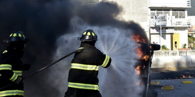 Firefighters try to put out a blazing car after students set the Municipal Palace on fire in Chilpancingo,...