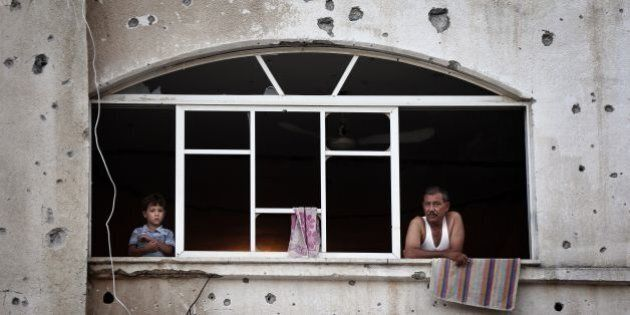 Palestinians look out of a window frame in their destroyed neighbourhood in the northern Gaza Strip city...