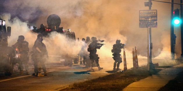 FERGUSON, MO - AUGUST 18: Police attempt to control demonstrators protesting the killing of teenager...