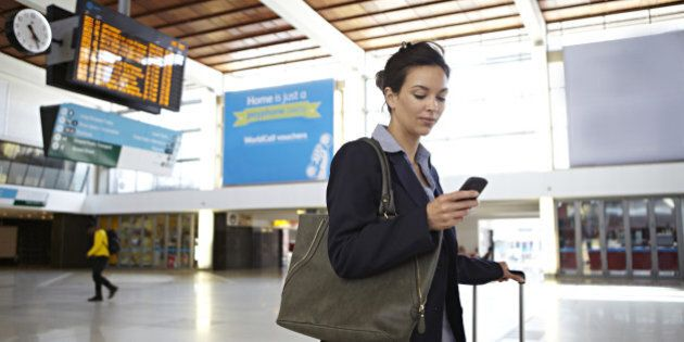 Businesswoman looking at smart phone in train station