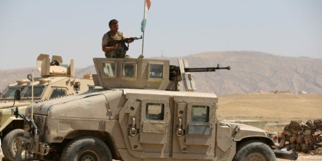 An Iraqi Kurdish Peshmerga fighter sits atop of an armed military vehicle as he monitors the area from...