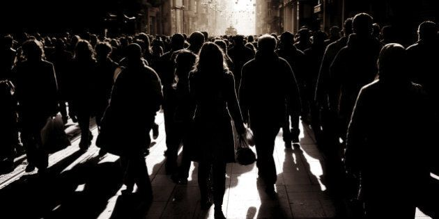silhouetted people walking on busy street in
