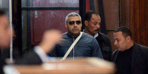 Qatar-based Al-Jazeera English journalist Egyptian-Canadian Mohamed Fahmy (C) arrives at the court in...