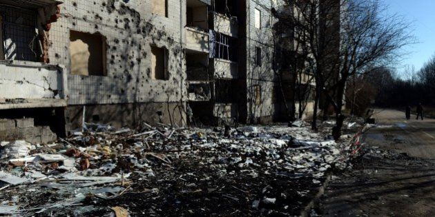 Pedestrians walk past a damaged building in Donetsk, on February 12, 2015. Russian President Vladimir...