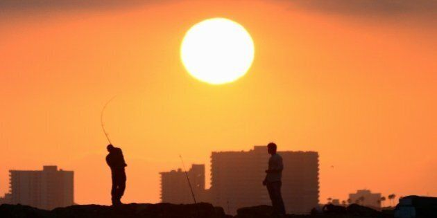 A fisherman casts his line from the rocks at Seal Beach, California, as the sun prepares to set on June...