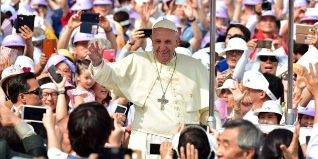 Catholic worshippers greet Pope Francis (C) as he arrives at Gwanghwamun Square in central Seoul on August...