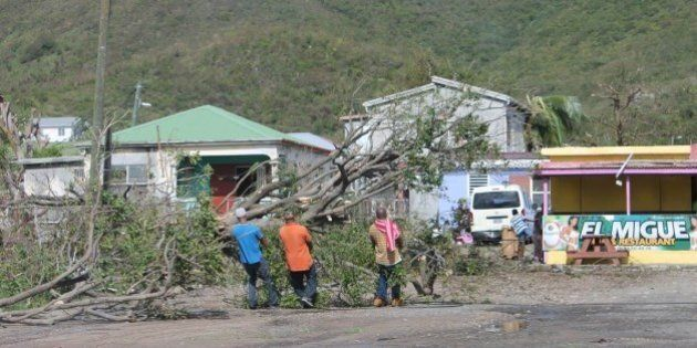 People clear trees from the road in the aftermath of the hurricane Gonzalo on October 14, 2014 on the...