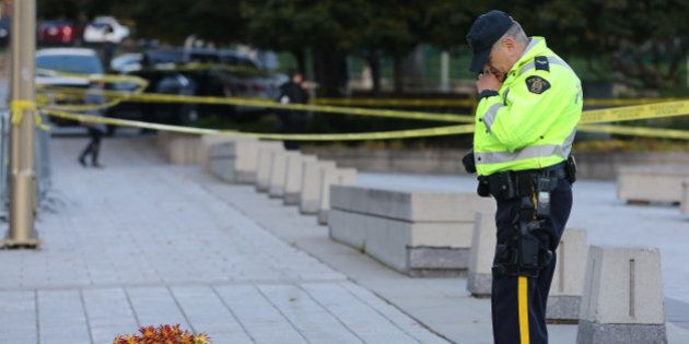 OTTAWA, ON- OCTOBER 23 - A RCMP officer looks at floral tributes to Cpl. Nathan Cirillo. Police continue...