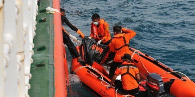 In this photograph taken on February 2, 2015, Indonesian rescue personnel from the National Search and Rescue Agency recover a body from the underwater wreckage of the ill-fated Air Asia flight QZ8501 in Java sea.  Indonesian divers on February 2 found another six victims of the AirAsia plane crash, an official said, taking to 84 the number of bodies retrieved since the accident in late December. AFP PHOTO / CHRISTIAN RIBUT        (Photo credit should read CHRISTIAN RIBUT/AFP/Getty Images)