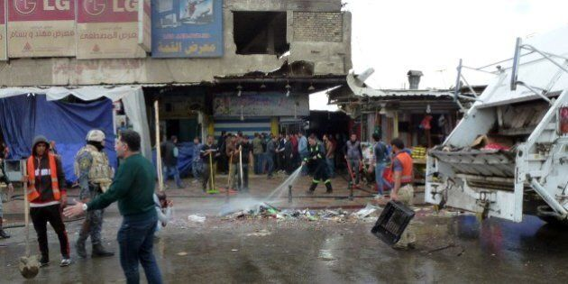 Iraqi's clean the street after a suicide bomber detonated explosives inside a restaurant in Baghdad al-Jadida, east of the capital, on February 7, 2015. Bombings in the Iraqi capital killed at least 17 people, hours before a years-old nightly curfew is due to be lifted, officials said. AFP PHOTO/SABAH ARAR        (Photo credit should read SABAH ARAR/AFP/Getty Images)