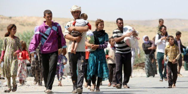 Displaced Iraqis from the Yazidi community carry their children as they cross the Iraqi-Syrian border...