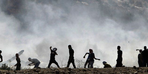 Palestinian protesters clash with Israeli security forces (unseen) following a demonstration in support...