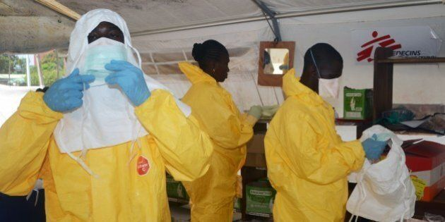 A picture taken on June 28, 2014 shows members of Doctors Without Borders (MSF) putting on protective gear at the isolation ward of the Donka Hospital in Conakry, where people infected with the Ebola virus are being treated. The World Health Organization has warned that Ebola could spread beyond hard-hit Guinea, Liberia and Sierra Leone to neighbouring nations, but insisted that travel bans were not the answer. To date, there have been 635 cases of haemorrhagic fever in Guinea, Liberia and Sierra Leone, most confirmed as Ebola. A total of 399 people have died, 280 of them in Guinea. AFP PHOTO / CELLOU BINANI        (Photo credit should read CELLOU BINANI/AFP/Getty Images)