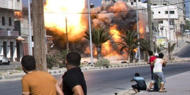 Palestinian men look on as a bomb from an Israeli air strike hits a house in Gaza City on August 23,...