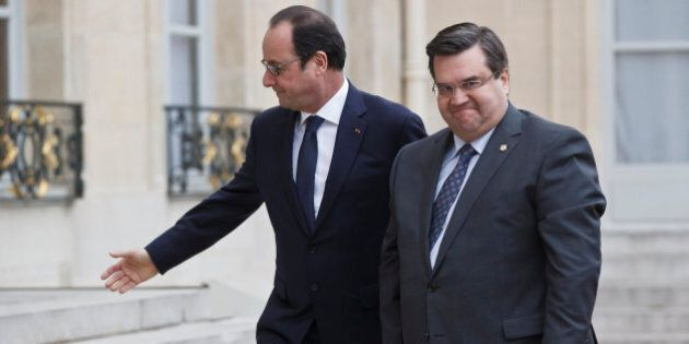 French President Francois Hollande, left, welcomes Montreal Mayor Denis Coderre, right, at the Elysee...