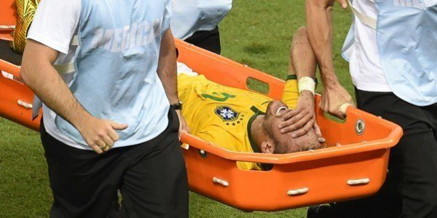 Brazil's forward Neymar is taken out on a stretcher during the quarter-final football match between Brazil...