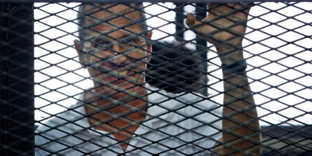 Al-Jazeera journalist Peter Greste looks out from the defendant's cage during the sentencing hearing...