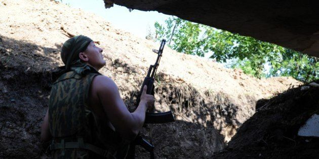 A pro-Russia militant stands in a trench as he takes shelter from bombing by a Ukrainian army plane near...