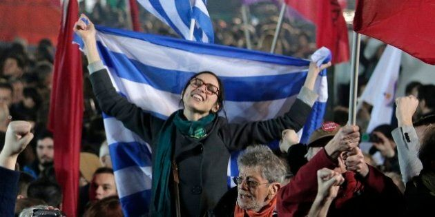 A supporter of Alexis Tsipras leader of Syriza left-wing party holds the Greek flag during a rally outside...