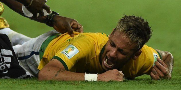 Brazil's forward Neymar (C) lies on the pitch after being injured during the quarter-final football match...