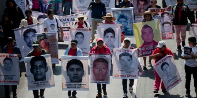 Relatives and protestors carry banners with pictures of some of the 43 missing students from a rural...