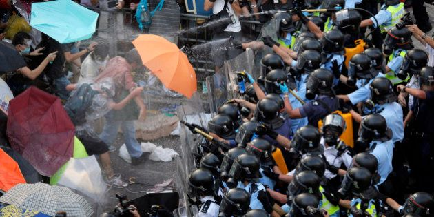 Riot police use pepper spray against protesters after thousands of people block a main road to the financial...
