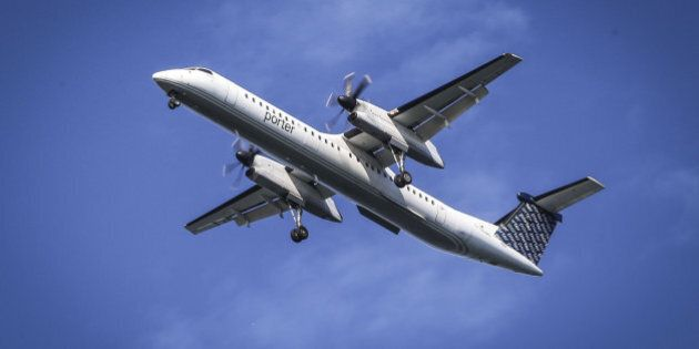 TORONTO, ON- AUGUST 27 - A Porter airlines Q400 with it's wheels down on final approach passes over Cherry...
