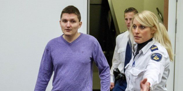 Russian defendant Vladimir Drinkman (L) is escorted by police officers at the courthouse in The Hague,...