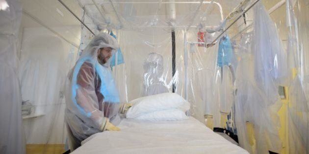 A nurse wears protective clothing as he demonstrates the facilities in place at the Royal Free Hospital in north London on August 6, 2014, in preparation for a patient testing positive for the Ebola virus. The specialised unit allows a team of doctors and nurses to provide care for anyone with the contagious condition. Despite it's high mortality level, Consultant Stephen Mepham advised against panic, stating that the chances of meeting an undiagnosed patient are virtually impossible with next to no chance of catching the virus without exposure to the sufferer's bodily fluids. AFP PHOTO/Leon Neal        (Photo credit should read LEON NEAL/AFP/Getty Images)